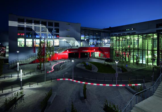 Rennstrecken-Atmosphäre: Die rot-weiß leuchtenden LED-Bodenlampen führen die ankommenden Besucher direkt zum »welcome center«. Foto: Trilux