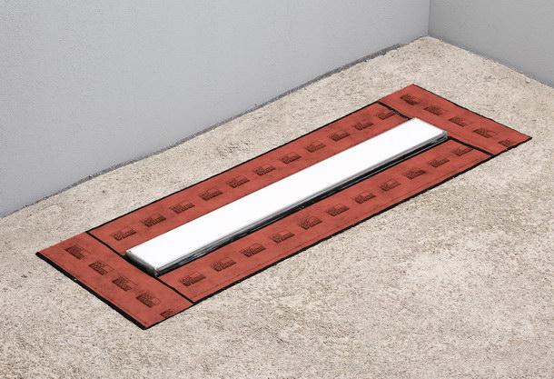 Überlappende »Seal System« Dichtbänder vor dem Auftragen der Verbundabdichtung.  Sie wirken als verbindendes Element zwischen Verbundabdichtung und der Duschrinne.