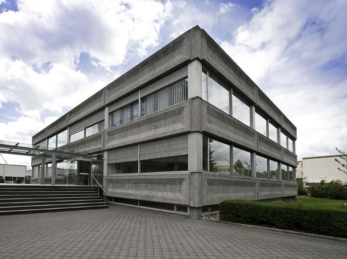 Verwaltungsgebäude vor der Sanierung mit Sichtbetonelementen und durchgehenden Fensterbändern