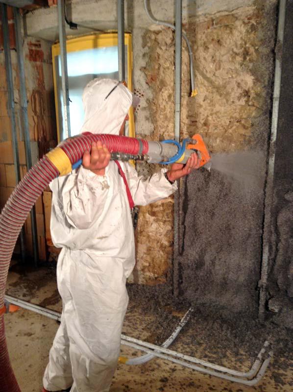 Mit einem geringen Kleberanteil werden die schadstoffgeprüften Cellulosedämmungen mittels Spezialmaschinen im Sprühverfahren auf die Innenwand aufgebracht. Foto: Climacell