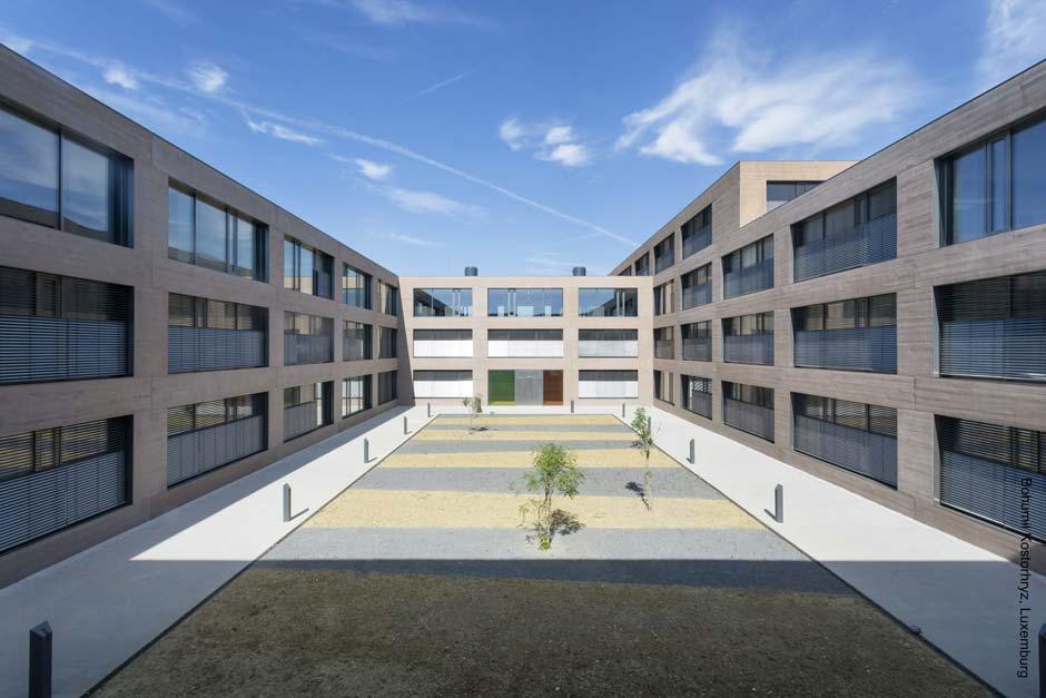 Einer der Innenhöfe zwischen den Gebäuden: Die Feldaufteilung der Lichtöffnungen folgt einem durchgängigen Prinzip. Pro Einheit sind zwei großflächige, automatisierte Lüftungselemente mit verdeckten Rahmenkonstruktionen mit einem schmalen, per Hand zu öffnenden Flügel kombiniert. Bild: Bohumil Kostohryz, Luxemburg