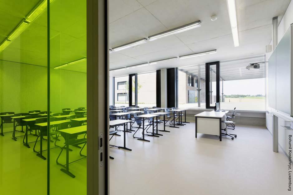 Die Klassenräume bieten eine helle, lernfreundliche Atmosphäre, klimatisch unterstützt durch hochwärmegedämmte Fenstertechnik sowie automatisierte Belüftung und Beschattung. Die großzügigen Aussichten auf Freiflächen, begrünte Innenhöfe und das Umland schaffen optische Übergänge zwischen Innen- und Außenraum. Bild: Bohumil Kostohryz, Luxemburg