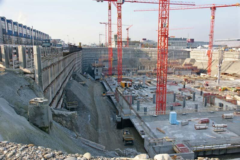 In der riesigen Baugrube arbeiten über 100 Personen an verschiedenen Bauteilen. Der Beton wird direkt an der Baustelle produziert und gelangt per Pumpleitung oder Fahrmischer und Betonverteiler zur Betonage.