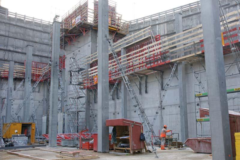 Hier werden die Wände mit der Mammut 350 auf Klapparbeitsbühnen geklettert, die Schächte mit der Schalung auf Kletterkonsolen KLK 230. Die vorfabrizierten Stützen im Vordergrund werden mit der Triplex R gestützt.