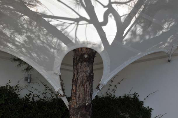 Gekonnt wurde der alte Baumbestand in das Sonnendach integriert. Dazu wurden die Sefar-Gewebe entsprechend bogenförmig ausgeschnitten und um die knorrigen Stämme arrangiert.