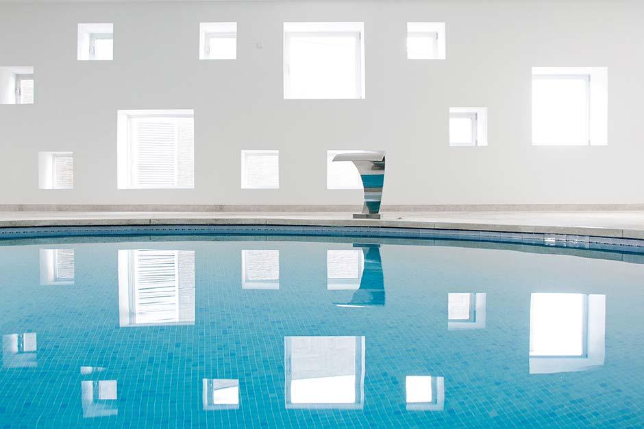 Die geschickt, unregelmäßig platzierten Velux Flachdach-Fenster erzeugen ein Lichtmuster, das sich tanzend auf der Wasseroberfläche wiederspiegelt. Foto: Velux / Laura Torres Roa & Antonio Benito Amengual
