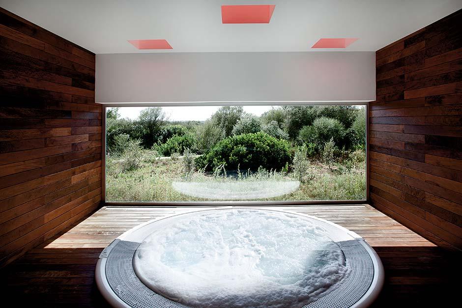 Ein Gefühl wie draußen: Die großen Panorama-Fenster ermöglichen beim Entspannen im Spa-Bereich einen Blick auf die umliegende Natur. Foto: Velux / Laura Torres Roa & Antonio Benito Amengual