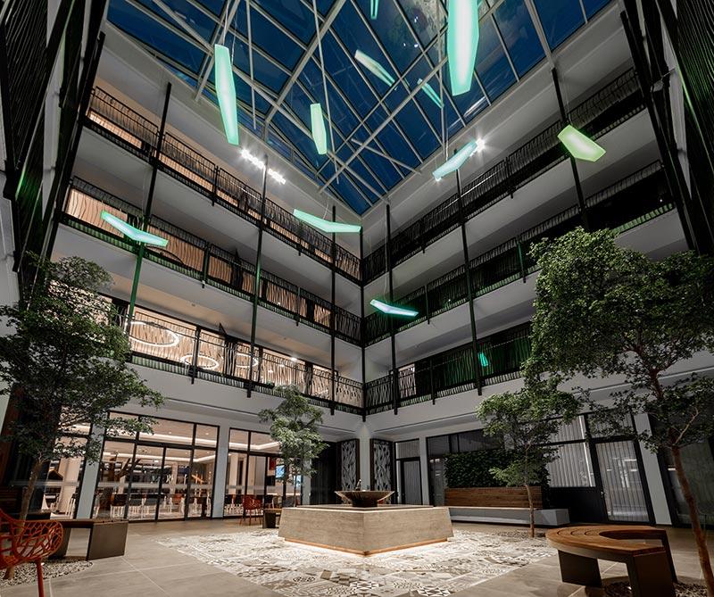 Die Beleuchtung der vier Olivenbäume im Herzstück des Neubaus wird mit Strahlern realisiert, die zurückhaltend an allen vier Seiten unterhalb der Glaskuppel montiert sind. Bildquelle: Berli Berlinski
