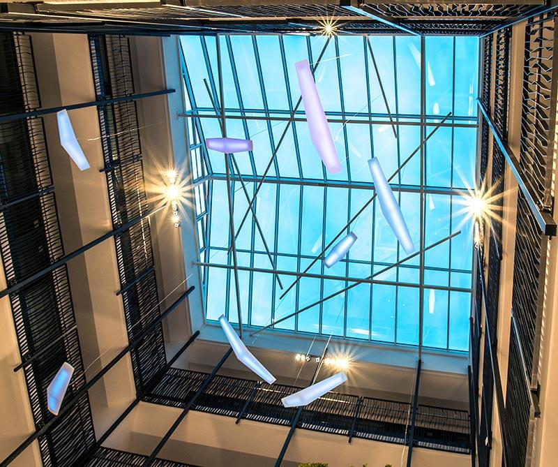 """Im Wintergarten unregelmäßig von der Glaskuppel abgependelte """"Vögel"""" wechseln über den Tag und die Woche die Farbe ihres Lichts. Sie bringen ein fröhliches, spielerisches Element in den Raum. Bildquelle: Michael Bamberger"""